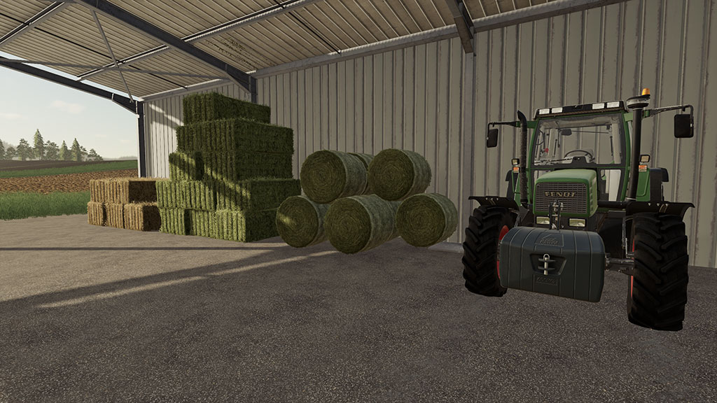 Bales stacked, protected by a shed